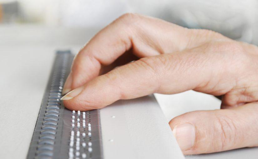 Hand auf einer Braille-Zeile für den Computer