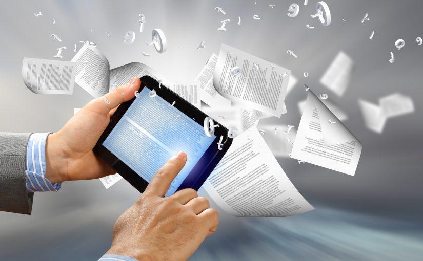 2 Hände halten ein Tablet mit Text, Zettel und Buchstaben fliegen herum